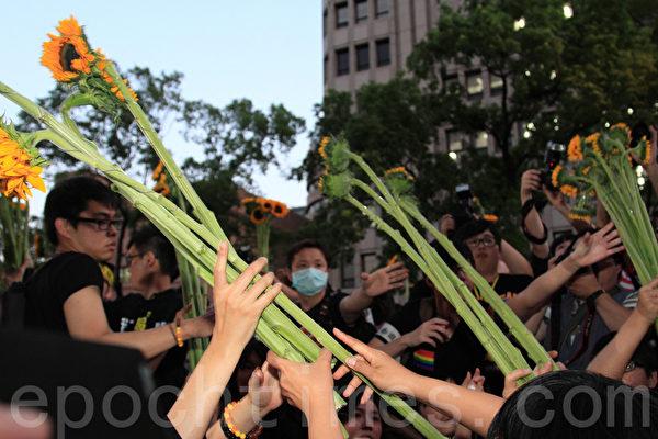 4月10日下午六點,太陽花學運正式撤出立法院,進入濟南路會場,與議場外志工交換花、相互擁抱,將花往外傳遞給其他人。(羅正恆/大紀元)