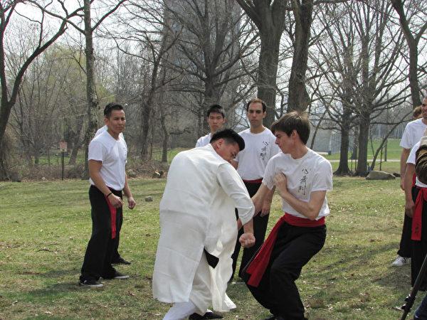 心武门教练带领学生在湖边演练武术中的拳法。(任倩雪/大纪元)