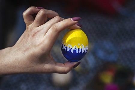 烏克蘭女子手持一顆復活蛋。 (DIMITAR DILKOFF/AFP/Getty Images)