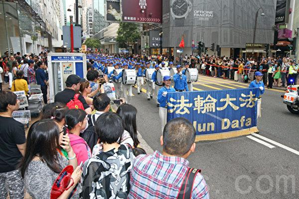 """香港法轮功学员4月20日举行声势浩大的游行,纪念""""四.二五""""和平大上访15周年,大约八百人游行队伍沿着九龙的闹市区,途经多个大陆游客购物热点,吸引两旁的大批游客观看,许多人拿着手机和相机争相拍摄。(潘在殊/大纪元)"""