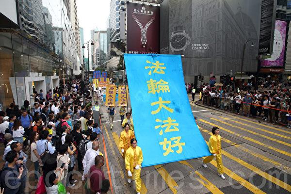 """香港法轮功学员4月20日举行声势浩大的游行,纪念""""四.二五""""和平大上访15周年,大约八百人游行队伍沿着九龙的闹市区,途经多个大陆游客购物热点,吸引两旁的大批大陆游客观看,许多人拿着手机和相机争相拍摄。(潘在殊/大纪元)"""