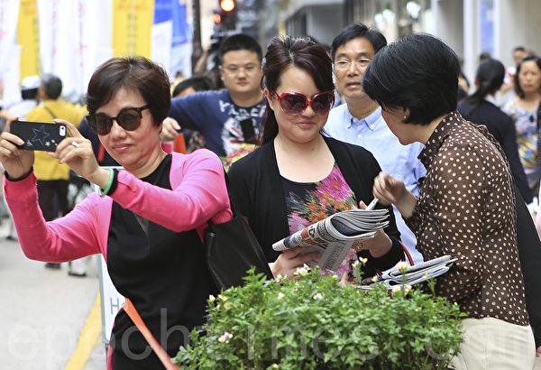 """香港法轮功学员20日在长沙湾举行""""四二五""""15周年反迫害集会游行,途中经过市中心旺角、尖沙咀,吸引了大批港民和大陆游客观看。(余铭/大纪元)"""