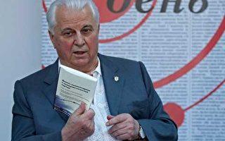 烏克蘭第一任總統列昂尼德•克拉夫丘克手持俄文版《九評》,在向《日報》的媒體人做介紹推薦。(網絡圖片)