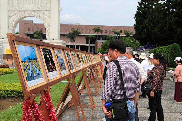 2014年4月26日,台灣法輪功學員於台北中正紀念堂、自由廣場進行排字活動,並對來往民眾洪法、講真相。圖為民眾正在專心閱覽正法之路圖片展。(羅正恆/大紀元)