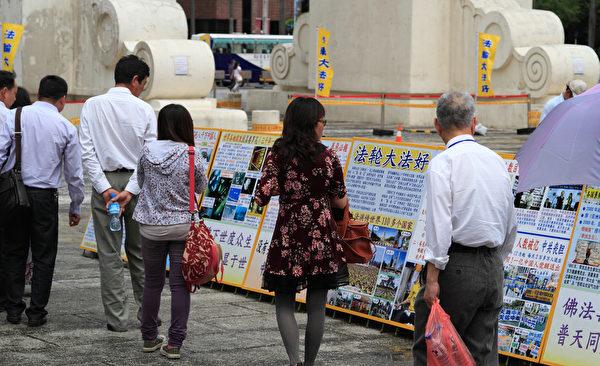 2014年4月26日,台灣法輪功學員於台北中正紀念堂、自由廣場進行排字活動,並對來往民眾洪法、講真相。圖為民眾正在專心閱讀展板。(羅正恆/大紀元)