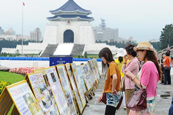 台灣法輪功學員4月26日在台北中正紀念堂舉行排字、煉功活動,並在一旁設有真相看板,吸引民眾駐足閱覽。(孫湘詒/大紀元)