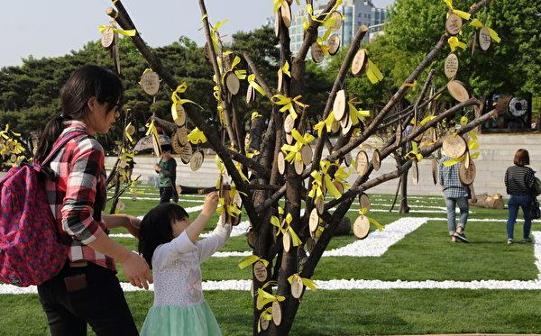"""2014年4月25日,高阳市国际花卉博览会上,市民们纷纷把自己写好的缅怀留言挂在""""希望之树""""上,以表达对""""岁月号""""沉船事件遇难者的哀悼。(全宇/大纪元)"""