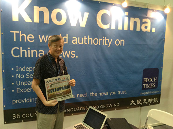 2014年4月24日,国际地产代理黄先生特意在大纪元《Know China》的展牌前留影,表示要把照片寄给地产开发商。(大纪元)