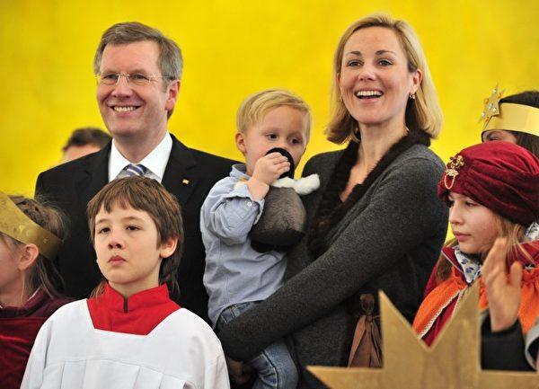 """2011年1月6日,伍尔夫和夫人在柏林总统府接待从汉堡来的""""三圣王歌手""""。每年德国的儿童歌手都通过唱歌为世界各地的慈善项目筹款。伍尔夫夫人怀中抱着的是他们两岁的儿子。(JOHN MACDOUGALL/AFP/Getty Images)"""