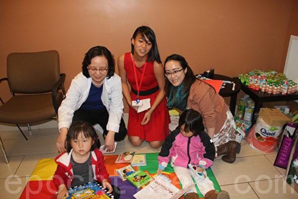 信义会华人家庭健康中心4月29日举办了讲故事与认字活动。图为医务主任赵秋衢(后排左一)、该中心义工、及孩子们合影留念。(王依澜/大纪元)