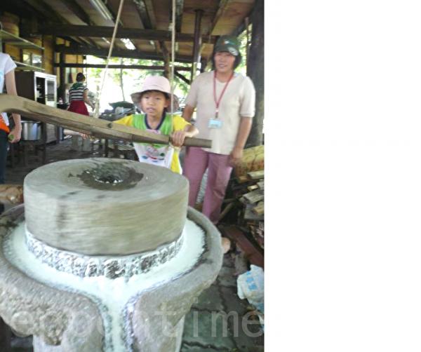 阿嬷的灶脚 孩子体验用石磨磨米。(岳明国小提供)