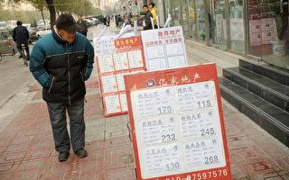 北京楼市近来出现了买家观望、卖家硬扛、中介关门的局面。图为北京一市民在房产中介门口看房屋价格牌。(GOU YIGE/AFP/Getty Images)