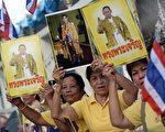 """2014年5月5日,泰王普密蓬(Bhumibol Adulyadej)登基64周年在华欣忘忧宫举行庆祝活动。图为泰国人拿着泰王照片,高喊""""国王万岁""""。(CHRISTOPHE ARCHAMBAULT/AFP/Getty Images)"""