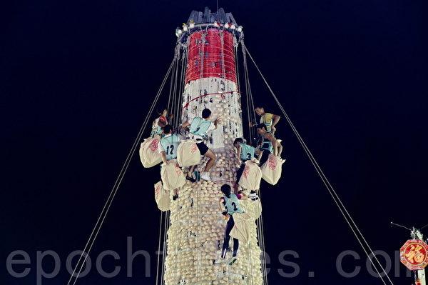 香港长洲太平清醮抢包山比赛于凌晨开始,成功晋身决赛的九男三女健儿迅速爬上包山,在三分钟内摘取最多包子,争夺奖项。(宋祥龙/大纪元)