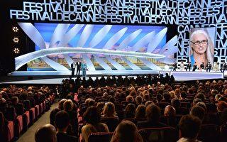 2014年5月14日晚,本届戛纳电影节主席、新西兰导演简•坎平(右)在开幕式上与作曲家迈克尔•尼曼、主持人朗贝尔•威尔森在台上致辞。(ALBERTO PIZZOLI/AFP/Getty Images)