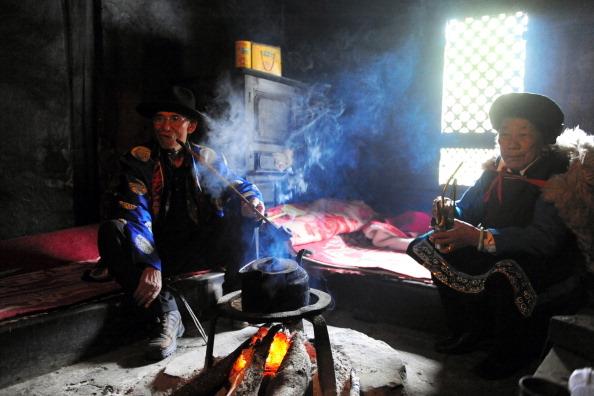 普米族处于云南边缘地区,婚期大多选在冬闲时节。图为两位普米族人坐在炕上。(图/Getty Images)