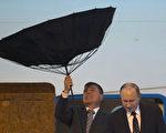 5月20日,俄羅斯總統普京在風雨中抵滬,下飛機時傘被大風吹折。普京當天還與中共前黨魁江澤民會見,當天官媒集體噤聲,微博「學習粉絲團」發消息,提普京講話,但江無話罕見成「啞巴」。(Ng Han Guan/AFP)