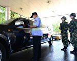 """5月20日,通往北京的某高速公路检查点,持枪武警协助安检人员检查过往车辆。""""六四""""临近,北京当局大为紧张。(STR/AFP)"""