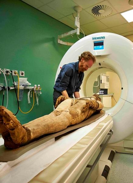 工作人員在用最新醫用CT掃瞄儀為一具木乃伊進行掃瞄(大英博物館提供)