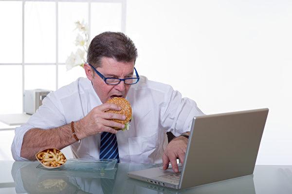 電子3C產品發出的背景藍光易刺激人的松果體產生飢餓感。邊吃邊看螢幕,讓你不知不覺狼吞虎嚥吃超量。(Fotolia)
