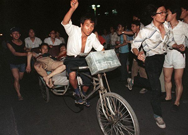 1989年6月4日,北京,被军人开枪射伤的学生被紧急载走。(MANUEL CENETA/AFP/Getty Images)