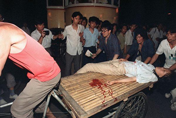 1989年6月4日,北京,被軍人開槍射傷的學生被緊急載走。(MANUEL CENETA/AFP/Getty Images)