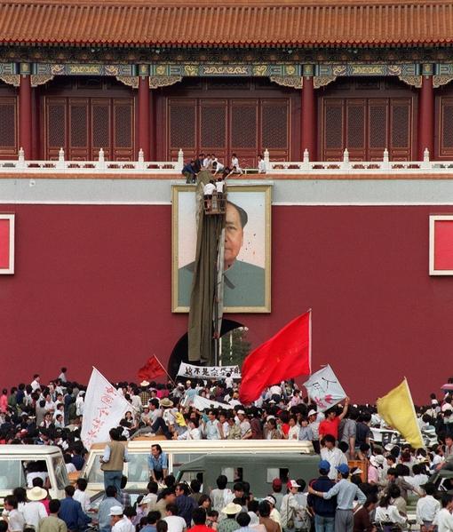 1989年5月23日,三名来自湖南的抗议者用带染料的鸡蛋击中天安门城楼上的毛泽东像。(CATHERINE HENRIETTE/AFP/Getty Images)