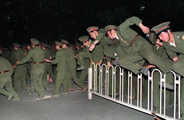 1989年6月4日凌晨,北京,荷枪实弹的军队在各地段与没有武装的学生与市民激烈冲突。(THOMAS CHENG/AFP/Getty Images)