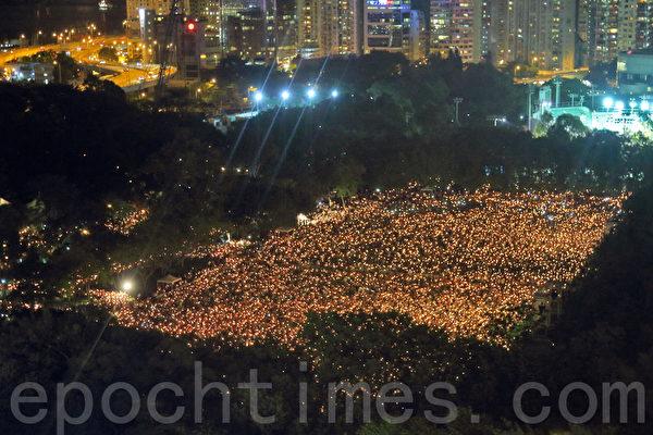 香港支聯會6月4日晚在維多利亞公園舉行六四燭光集會,大會宣布超過18萬人參加,是歷年來最多,支聯會呼籲民眾一起攜手平反六四,結束中共一黨專政,除六個足球場外,維園的草地也坐滿人。(潘在殊/大紀元)