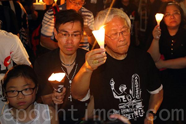 香港支聯會6月4日晚在維多利亞公園舉行六四燭光集會,大會宣布超過18萬人參加,是歷年來最多,支聯會呼籲民眾一起攜手平反六四,結束中共一黨專政,天主教香港前主教陳日君樞機(右一)首次參加燭光悼念集會。(潘在殊/大紀元)