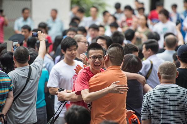 北京某考点外,考生步出考场后与家人抱成一团。(AFP)