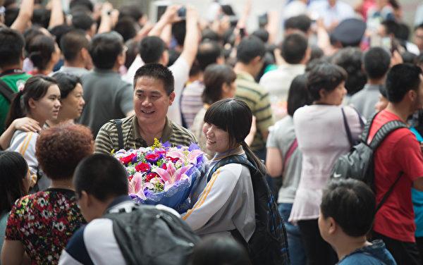 北京某考点外,家人用鲜花送给刚经历高考的女儿。(AFP)