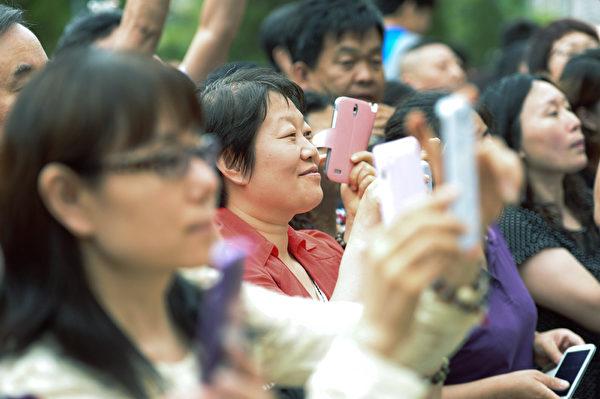 北京某考点外,父母们纷纷拿起电话记录子女人生关键时刻。(AFP)