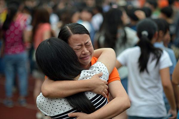 高考结束,重庆一女生拥抱老师,留下热泪。(AFP)