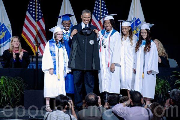 奥巴马总统和应届毕业生合影,同时展示毕业生赠送印有渥斯特科技高中校徽的运动外套。(徐明/大纪元)