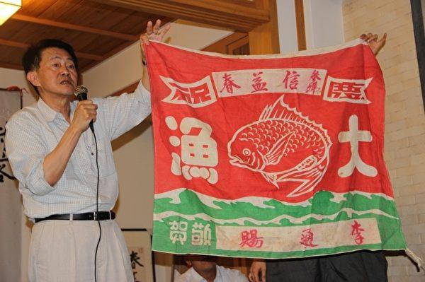 庄伯和拿着渔船要出港的旗帜。(谢月琴/大纪元)