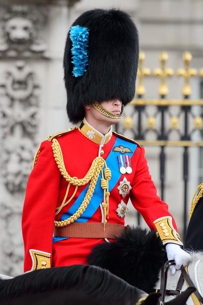 2014年6月14日,英女王生日慶典,威廉王子穿著紅色緊身制服,頭戴黑色熊皮帽,策馬參加遊行。(LEON NEAL/AFP/Getty Images)