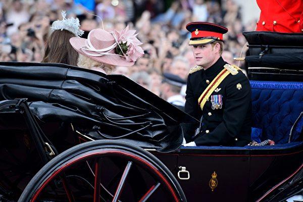 2014年6月14日,英女王生日慶典,哈里王子(右)與康沃尔伯爵(查爾斯王子)夫人卡米拉和劍橋伯爵夫人凱瑟琳(即凱特王妃)乘坐馬車穿過皇家騎兵衛隊閱兵場。(LEON NEAL/AFP/Getty Images)
