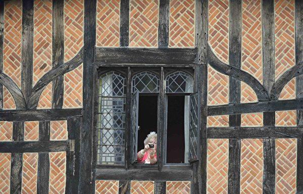 2014年6月16日,英王室一年一度的嘉德勳章授勳盛典期間,一位居民從溫莎堡中的一個棚屋中拍照。(Toby Melville - WPA Pool /Getty Images)