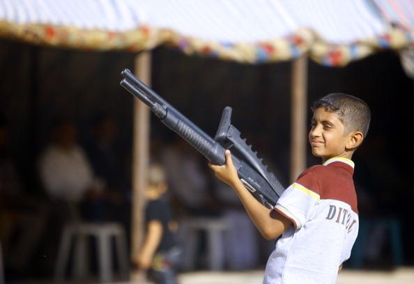 2014年6月17日,一名伊拉克儿童拿着武器,与部落族人聚集,展示他准备加入什叶派安全部队,与逊尼派叛军对抗。(HAIDAR HAMDANI/AFP/Getty Images)