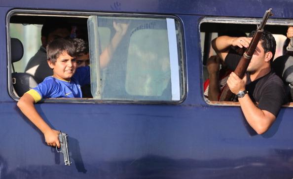 2014年6月16日,一名伊拉克儿童拿着手枪,搭乘运送志愿参战、保卫巴格达的人,加入安全部队。(AHMAD AL-RUBAYE/AFP/Getty Images)
