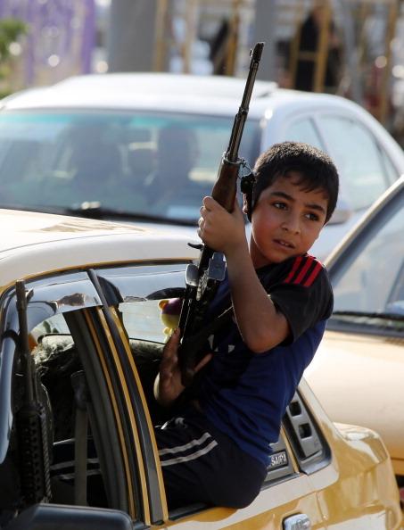 2014年6月16日,一名儿童拿着武器,坐在车窗上,展示他们准备加入安全部队,与逊尼派叛军对抗。(AHMAD AL-RUBAYE/AFP/Getty Images)
