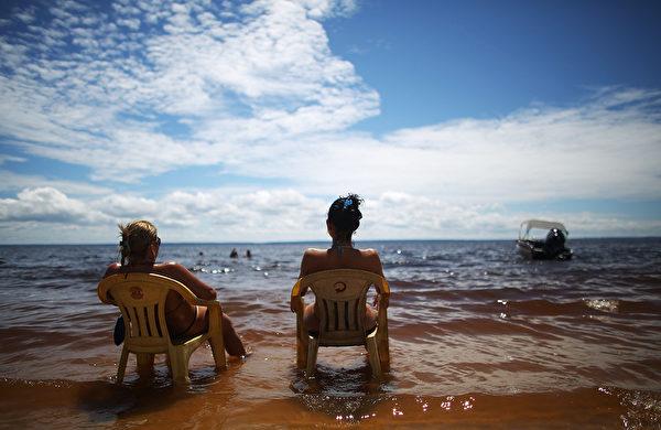 人们在巴西马瑙斯Praia da Lua海滩享受日光浴。(Mario Tama/Getty Images)