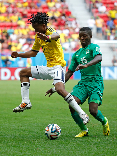 BRASILIA, BRAZIL - JUNE 19: Juan Guillermo Cuadrado of Colombia is challenged by Max Gradel of the Ivory Coast during the 2014 FIFA World Cup Brazil Group C match between Colombia and Cote D'Ivoire at Estadio Nacional on June 19, 2014 in Brasilia, Brazil.  (Photo by Gabriel Rossi/Getty Images)
