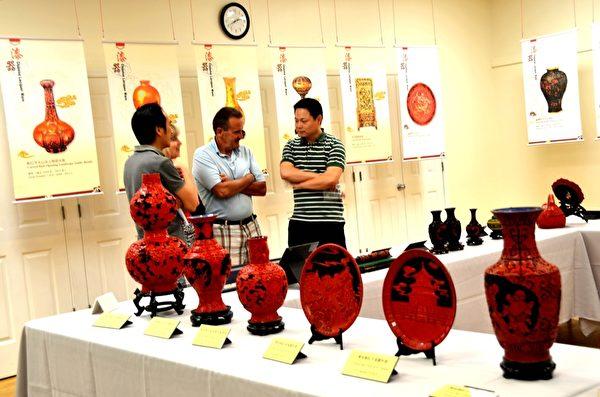 展出的中國漆器大部份是孫遜先生(右一)收藏的。圖為他正在為參觀者講解。(良克霖/大紀元)