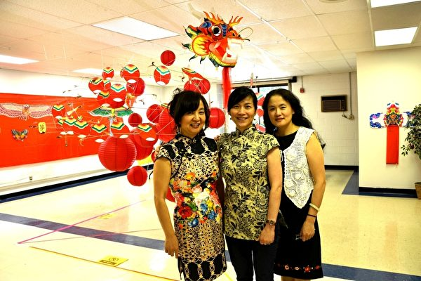 負責風箏展的張振(左一)、王樹紅(中)和張志英女士。她們身後是約20米長的龍頭蜈蚣風箏。(良克霖/大紀元)