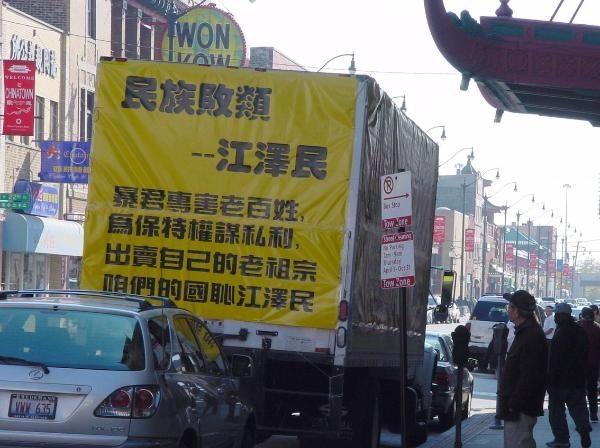 一輛「中國大赦」的巨型箱車駛過,車上印有江澤民和葉利欽熱烈擁抱的大幅圖片。江澤民雙手摟著葉利欽的脖子,笑容十分諂媚。旁邊則用特大號字寫著「民族敗類,千古罪人」,並附有江澤民黑箱作業出賣大片北方國土給俄羅斯的示意圖。(大紀元資料圖片)