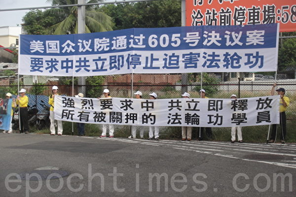 法轮功学员27日在高铁举横幅,要求中共停止迫害法轮功。(杨秋莲/大纪元)