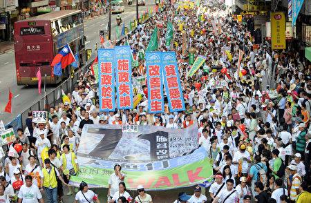 """2009年七一大游行的主题为""""施政失误、贫富悬殊、还政于民、改善民生""""。图为2009年7月1日,香港,参加游行的队伍。(MIKE CLARKE/AFP)"""