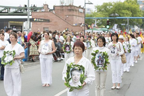 一組身著白衣的女法輪功學員,手捧用磁盤托起的照片.都是被中共迫害死的法輪功學員的遺像。(Matthias Kehrein/大紀元)